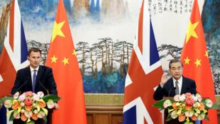 英国外交大臣亨特(左)与中国外交部长王毅举行记者招待会,2018年7月30日,北京