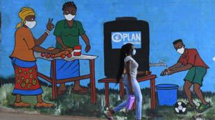 Una mujer pasa junto a un grafiti que promueve el lavado de manos y el uso de mascarillas contra el covid-19 en Kibera, Nairobi (Kenia), el 13 de agosto de 2020