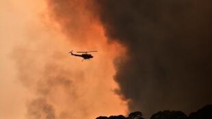 Um helicóptero sobrevoa área incendiada perto de Bilpin, 90 km a noroeste de Sydney, na Austrália, em 19 de dezembro de 2019.