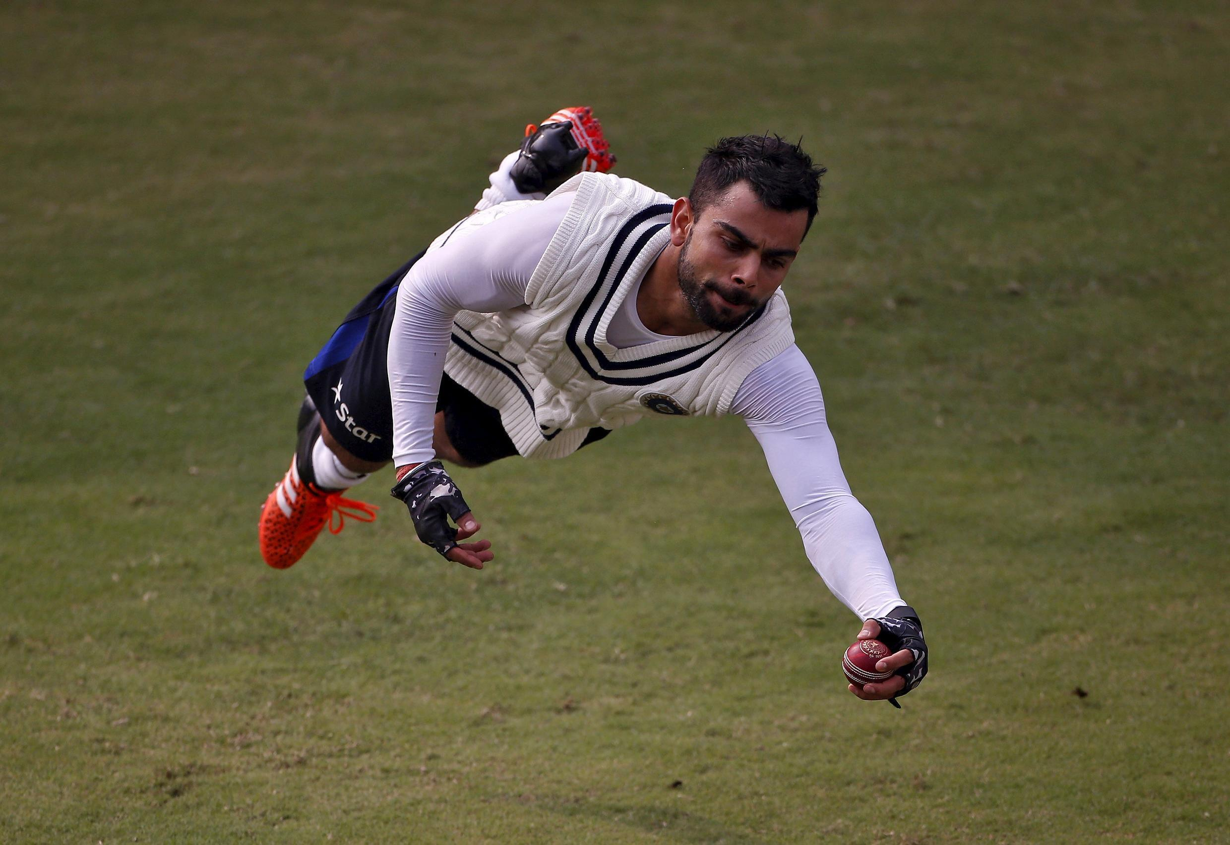 Indian cricket captain Virat Kohli takes a diving catch during a fielding practice session on the eve of the fourth test match against South Africa in New Delhi on Thursday.