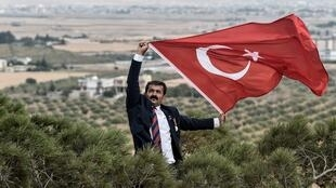 Man waves a Turkish national flag in front of the Syrian town of Ras al-Ain