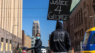Devant le tribunal où Derek Chauvin est jugé, un manifestant brandit une pancarte sur laquelle on peut lire: «Justice pour George», le 29 mars 2021.