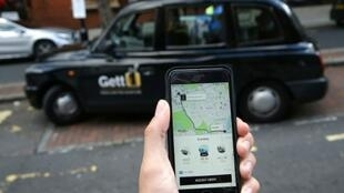 A customer scans Uber's ride-sharing app near a black cab in London where the company won a 15-month licence reprieve in return for changing some of its practices