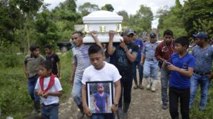 Un niño lleva una foto de la Jackeline Caal, niña de 7 años que falleció dos días después de ser detenida por agentes de la frontera americana