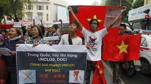 Anti-China protesters hold Vietnamese national flags and anti-China banners while marching on a street in Hanoi December 9, 2012.