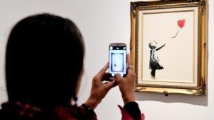 «La petite fille au ballon», du street artist Banksy, ici en 2016 lors de l'exposition « Guerra, Capitalismo & Liberta » à Rome. Le graffiti du même nom vient d'être désigné « œuvre préférée des Britanniques », selon un sondage publié le 26 juillet 2017.