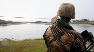 Soldiers stand guard on a bank of a polluted tributary in Gokana, Nigeria, during the launch of an exercise to clean up pollution in Ogoni land