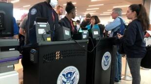 Un officier de police, protégé par un masque anti-viral, vérifie les passeports à l'aéroport de Fort Lauderdale.