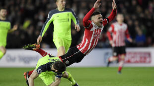 Southampton's Dusan Tadic goes down after a challenge from Liverpool's James Milner in their match on Wednesday.