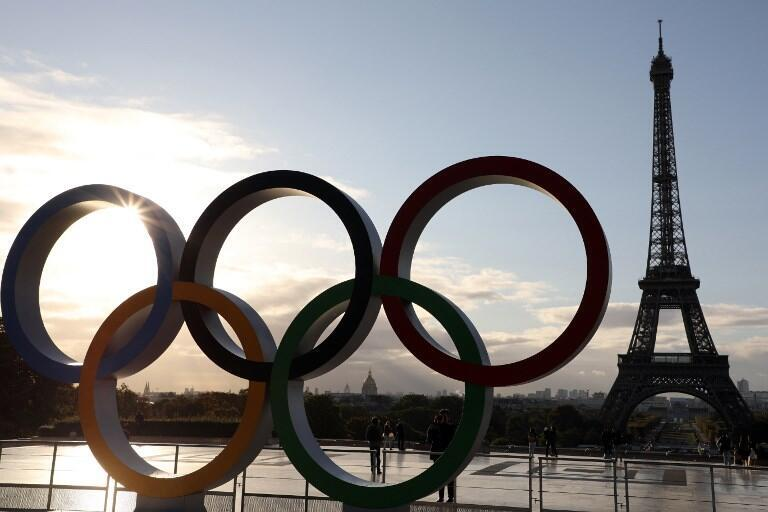 People take pictures of the Olympic rings installed on the Esplanade du Trocadero near the Eiffel tower following the Paris' nomination as host for the 2024 Olympics, on September 14, 2017 in Paris.