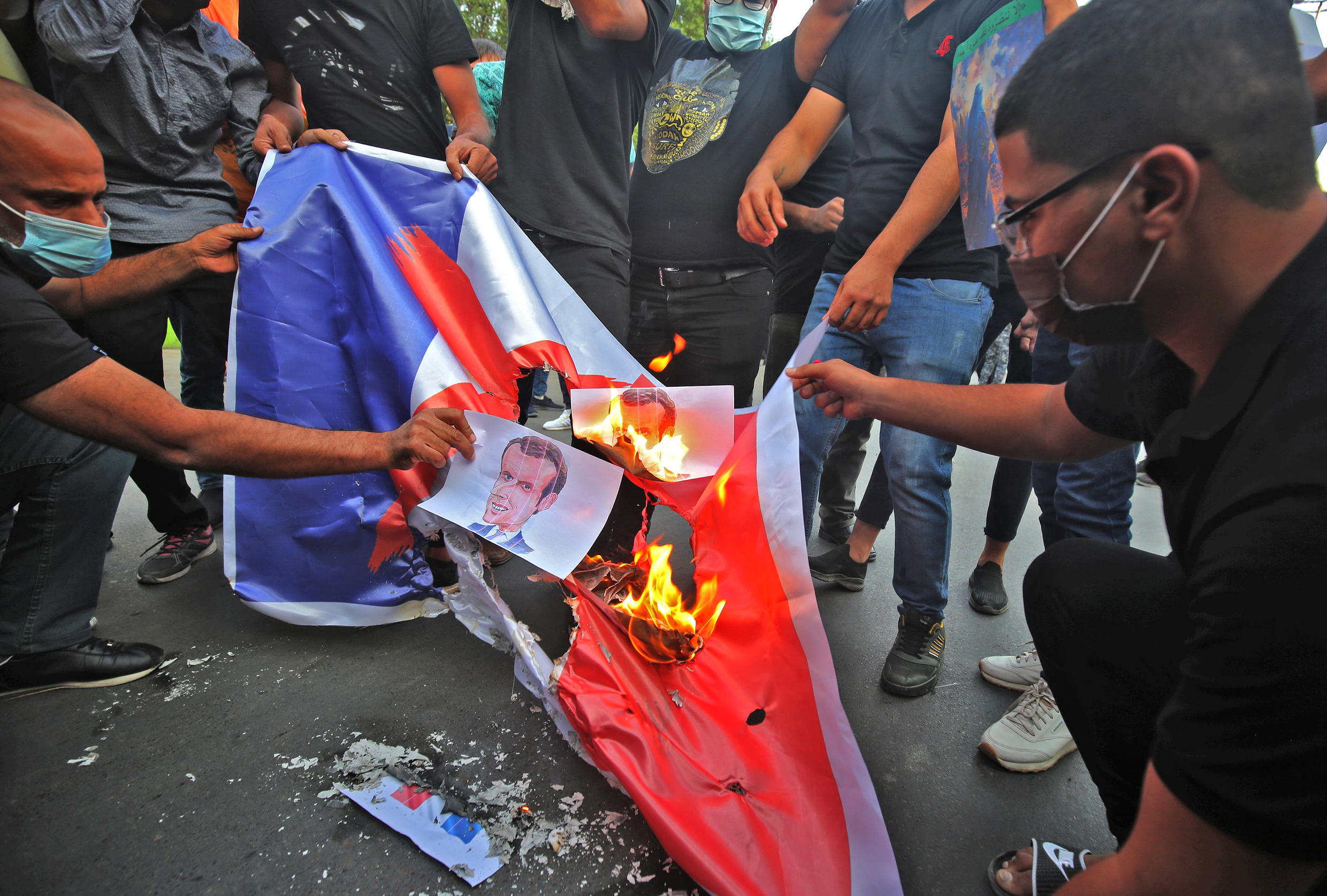 Iraqi protesters burn posters and the French flag during a demonstration against French President Emmanuel Macron in front of the French embassy in Baghdad on October 26, 2020
