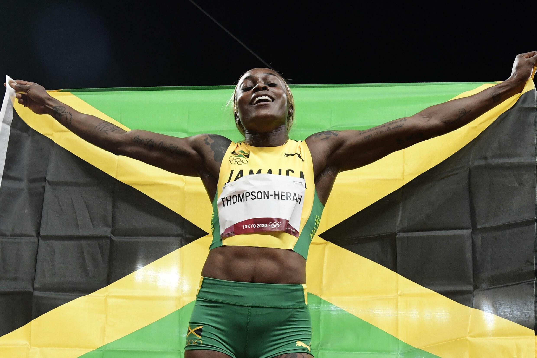 Elaine Thompson-Herah celebra su triunfo en la final de los 100 metros lisos de los Juegos Olímpicos con una bandera de Jamaica, el 31 de julio de 2021 en Tokio