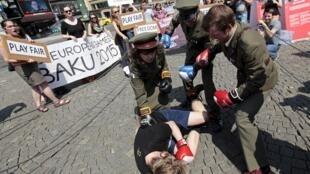 Mise en scène de violences policières par des militants pro-démocratie à Prague, lors d'un rassemblement contre la tenue des Jeux européens à Bakou.