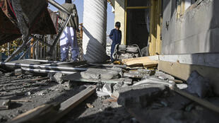 Residents inspect a damaged house in Khair Khana after the rocket attack on Kabul