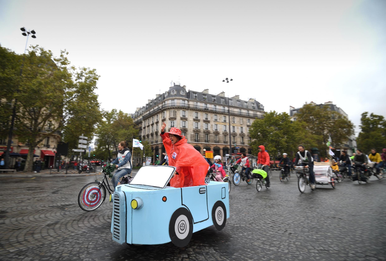 "A woman rides a cardboard car on Place de la Bastille during a ""car free"" day in Paris."