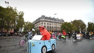 "A woman rides a cardboard car on Place de la Bastille during a ""car free"" day in Paris."