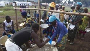 Des réfugiés de RDC attendent la distribution de nourriture (novembre 2013), au centre de transit de Nyakabande, dans le secteur de Kisoro (Ouganda).