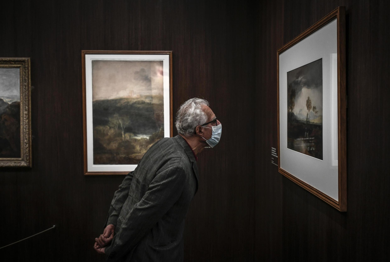 Un visiteur masqué regarde un tableau de William Turner, au musée Jacquemart-André à Paris, le 26 mai 2020.
