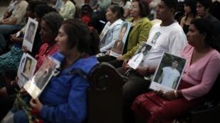 Madres muestran fotos de sus hijos desaparecidos, este 13 de octubre en Guatemala.