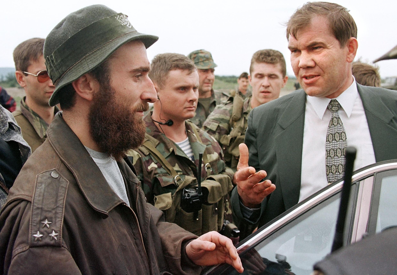 Российский генерал Александр Лебедь (справа) в окружении телохранителей беседует с одним из чеченских командиров, Ширвани Басаевым, братом Шамиля Басаева, Старые Атаги, 31 августа 1996.