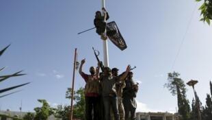 La Russie pilonne les positions du groupe EI mais aussi celles du Front al-Nosra, dont un combattant hisse sur cette photo le drapeau de l'organisation dans la ville de Ariha, en mai 2015.