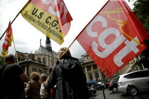 People wave flags of French union confederation Confederation generale du travail (CGT) during a demonstration in front of the Courthouse in Paris on June 16, 2016.
