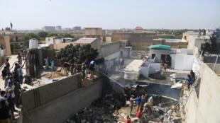 Unos socorristas echan agua sobre unos restos del avión de Pakistan International Airlines que se estrelló en un barrio residencial de Karachi, el 22 de mayo de 2020 al sur de Pakistán