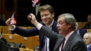 Le leader du parti Brexit Nigel Farage agite un drapeau britannique après le vote au Parlement européen, le 29 janvier 2020.