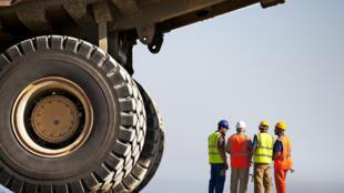 Travailleurs parlant de machines sur un chantier.