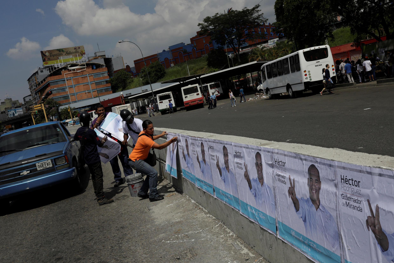Ciudadanos colocan afiches de cara a las elecciones a gobernador en Caracas, el 6 de octubre de 2017.