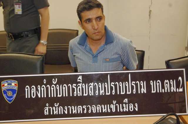 Mohammad Hazaei, de 42 años, sentado detrás de un cartel de la oficina de imgración luego de ser arrestado en el aeropuerto de Bangkok, el 14 de febrero de 2012.