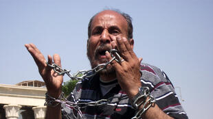 A revolution in chains - protester outside the Constitutional Court, Cairo, 14 June, 2012
