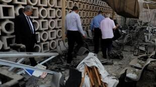 Des enquêteurs devant la façade endommagée de l'Institut national du cancer au Caire après l'explosion, le 5 août 2019.