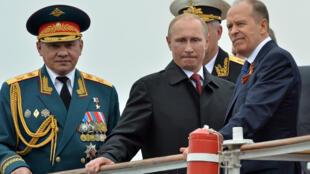 Le président russe Vladimir Poutine, entouré par son ministre de la Défense Sergueï Choïgou (g) et le patron du FSB Alexandre Bortnikov, en 2014 dans le port de Sébastopol, en Crimée.