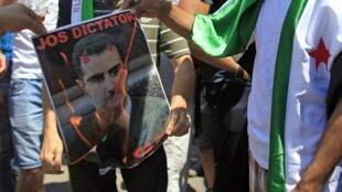Wani dan Syria ya cinna wa  Hoton shugaban kasa Bashar Assad wuta