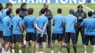Pep Guardiola, técnico do Barcelona, passa instruções a seus jogares durante treino no estádio de Nou Camp, na cidade espanhola homônima, nesta segunda-feira.