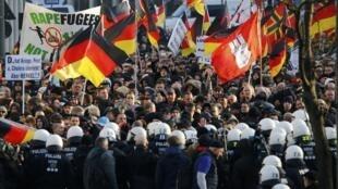 """تظاهرات مخالفان سیاست پناهندگی دولت، در برابر ایستگاه مرکزی راهآهن شهر کلن که به دعوت گروه خارجی ستیز و به ویژه اسلام ستیز """"پگیدا"""" صورت گرفته. ١٩ دی/ ٩ ژانویه ٢٠١٦"""