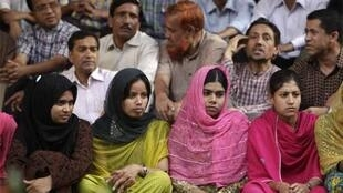 Grameen employees sit in in front of their central office in protest at the Supreme Court decision