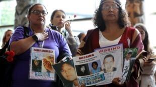 Mujeres indígenas exhiben carteles durante la ceremonia de clausura de la investigación nacional sobre las mujeres y niñas autóctonas desaparecidas y asesinadas. El 3 de junio, en Quebec.
