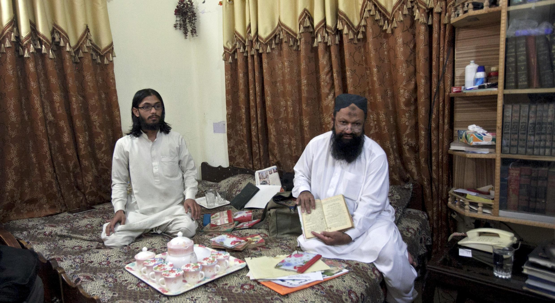 """資料圖片:巴基斯坦激進伊斯蘭武裝""""羌誠軍""""頭領馬立克-伊沙克(右)與兒子烏斯曼(左)2012年10月9日在旁遮普邦南部的家中接受路透社記者採訪。"""