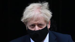 Boris Johnson, con mascarilla negra, sale de su residencia oficial del número 10 de Downing Street para dirigirse a la sesión semanal de control parlamentario, el 4 de noviembre de 2020 en Londres