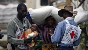 Des humanitaires congolais du CICR aident des déplacés qui s'apprêtent à recevoir une aide alimentaire, à Kibati, le 5 novembre 2008.