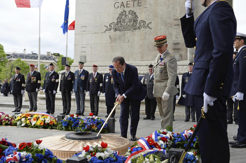 O presidente francês, François Hollande, acende chama em homenagem ao soldado desconhecido no Arco do Triunfo, em Paris.