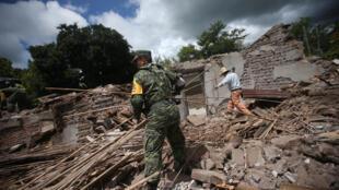 Un soldado y un residente limpian los escombros de un casa destruida por el terremeto en San Juan Pilcaya, en la zona del epicentro, México, el 25 de septiembre de 2017.