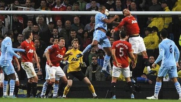 Nahodha wa Manchester City Vincent Kompany akipiga kichwa mbele ya beki wa Manchester United Chris Smalling na kuipa ushindi timu yake