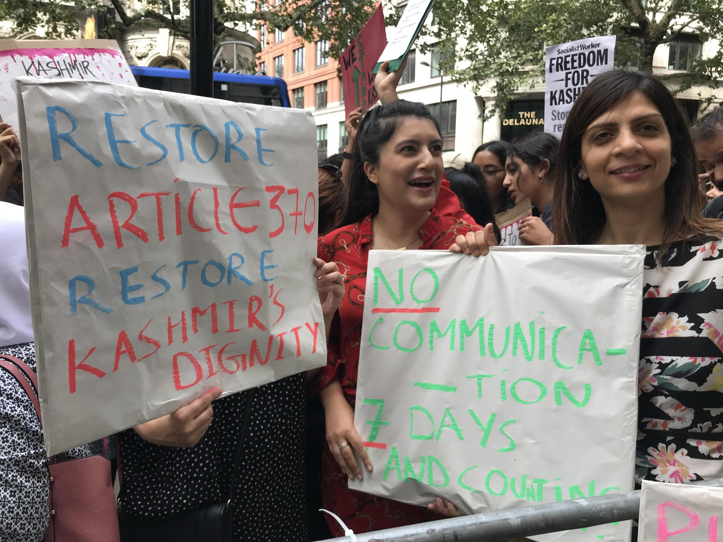 Protesters in London hold signs expressing solidarity with Kashmir after India scrapped the region's special constitutional status, August 10, 2019.