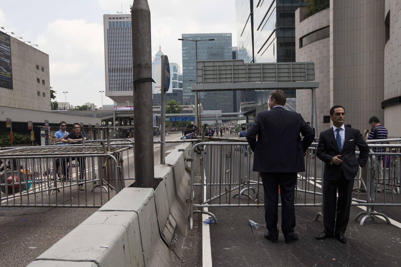 Des hommes d'affaires, devant une route bloquée par les manifestants pro-démocratie, en plein centre du quartier de la finance, à Hong Kong, ce lundi 29 septembre, au matin.