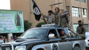 Picha ya propaganda iliyorushwa na vyombo vya habari vya kijihadi Welayat Raqa inaonyesha wapiganaji wa kundi la Islamic State wakifanya mazoezi ya kijeshi katika mitaa ya mji wa Raqa, Juni 30, 2015, Syria.