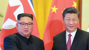 Le leader nord-coréen Kim Jong-un (g) reçu par le président chinois Xi Jinping, à Pékin, le 19 juin 2018.