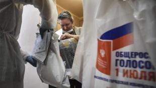 Una electora vota en el referéndum ruso depositando su papeleta en una urna móvil el 29 de junio de 2020 en su apartamento de Moscú